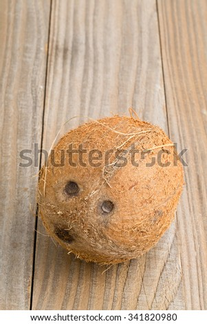Whole uncut coconut on wooden table background - stock photo
