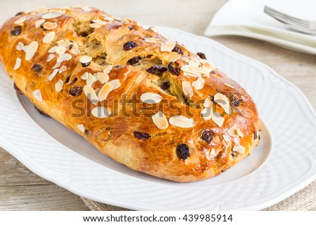 Whole, uncut fruit bread on white plate. Full with chocolate and dried fruits. - stock photo