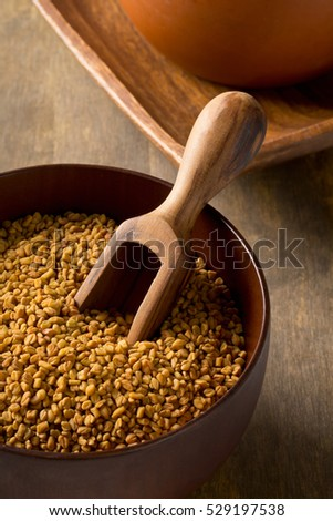 Whole unprocessed fenugreek (Trigonella foenum-graecumcumin) seeds in wooden bowl with scoop