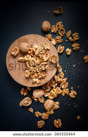 Whole Walnuts and Cleared Black Wooden Background Top view Healthy concept - stock photo