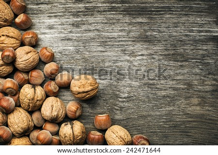 Whole walnuts and hazelnuts on a wooden background - stock photo