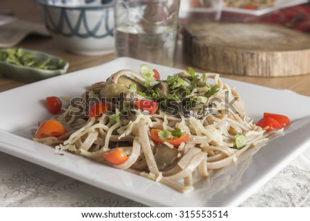 Whole wheat and ecological spaghetti with eggplant, cherry tomatoes and cilantro  - stock photo