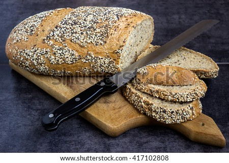 Whole wheat bread and rye, sprinkled with sunflower seeds, poppy seeds, sesame seeds, sliced with a knife on a board - stock photo