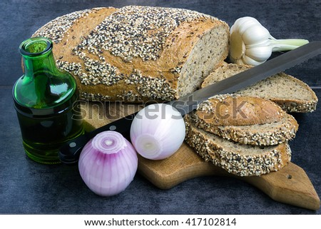 Whole wheat bread and rye, sprinkled with sunflower seeds, sesame seeds and poppy seeds, sliced on the board, next to the olive oil and onions - stock photo