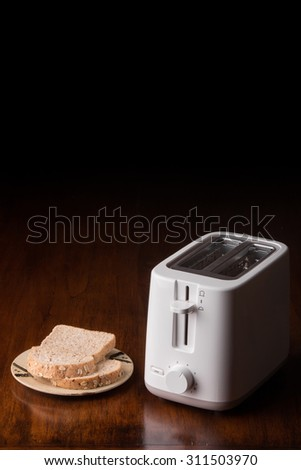 Whole wheat bread and white toaster on wooden table. - stock photo