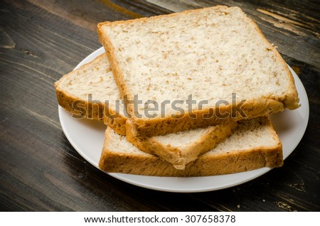 Whole wheat bread on wooden background,meal or breakfast - stock photo