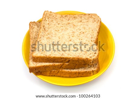 whole wheat bread on yellow plate isolated on white background