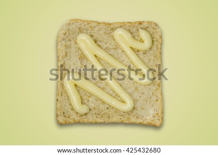 Whole wheat bread pour mayonnaise on color background / Bread Mayonnaise - stock photo