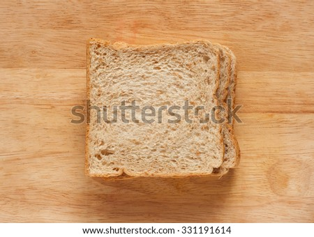 whole wheat breads on a wooden plank - stock photo