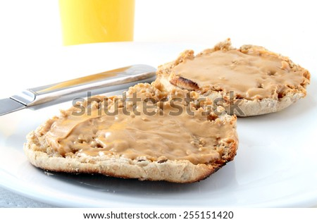 Whole wheat english muffin with peanut butter and orange juice. - stock photo