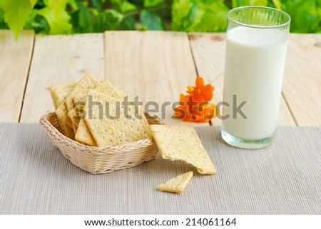 Whole wheat flour crackers and milk on wooden plank table with green summer background - stock photo