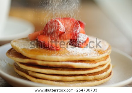 Whole wheat pancakes topped with strawberries and honey