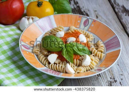 Whole wheat pasta with homemade tomato sauce and mini mozzarella. Garnished with fresh basil. On wooden table. Natural light. Selective focus.  - stock photo
