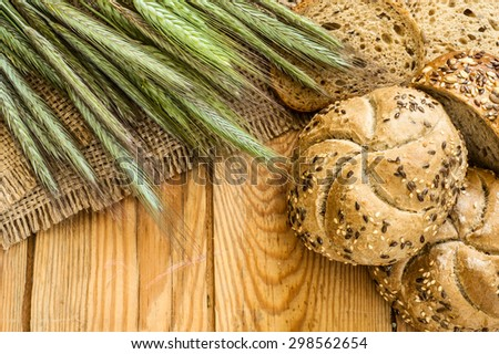 Whole wheat rye bread rolls with ears of cereal located on wood background. Rustic arrangement. - stock photo