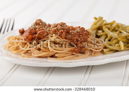 Whole wheat spaghetti with French style cut green beans on white wood - stock photo
