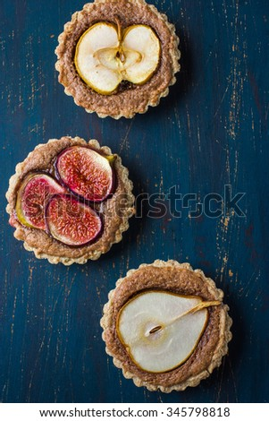 whole wheat tarts  with chocolate frangipane, fig, apple and pear, top view - stock photo