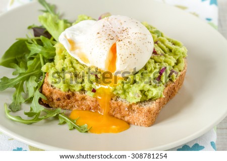 Whole wheat toasted bread with avocado and poached egg - stock photo