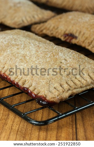 Whole wheat toaster pastries, lightly dusted with sugar crystals and filled with raspberry filling. - stock photo