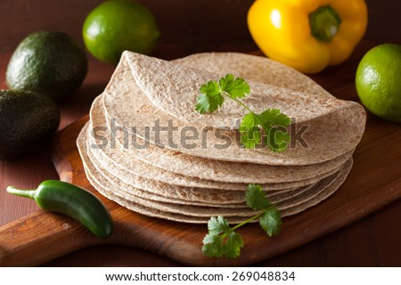 whole wheat tortillas on wooden board and vegetables - stock photo