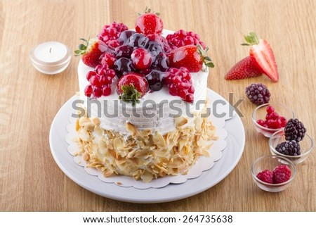 Whole White Berry Fruit Cake on Wooden Table - stock photo