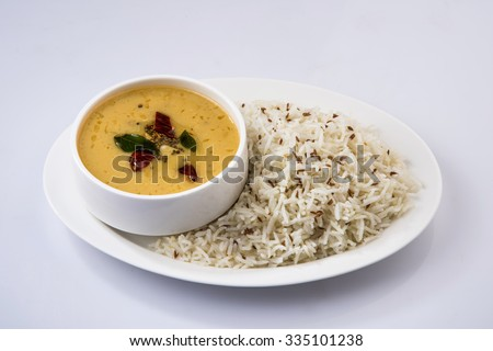 Whole Yellow Lentil with Rice, dal tadka and jeera rice, Indian Dish, cooked rice and cooked Arhar or Toor dal (Pigeon Pea), served in a white plate, isolated on white background  - stock photo