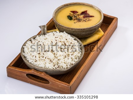 Whole Yellow Lentil with Rice, dal tadka and jeera rice, Indian Dish, cooked rice and cooked Arhar or Toor dal (Pigeon Pea), served in ceramic bowl in a tray, isolated view on white background  - stock photo
