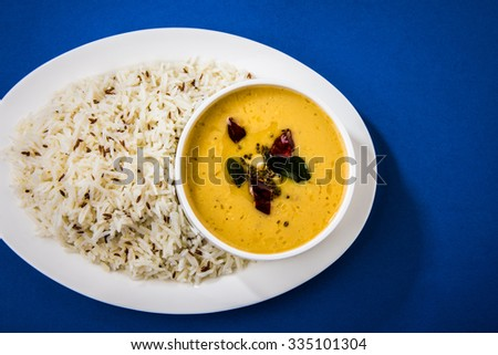 Whole Yellow Lentil with Rice, dal tadka and jeera rice, Indian Dish, cooked rice and cooked Arhar or Toor dal (Pigeon Pea), served in a white plate,cropped view on blue background, top view - stock photo