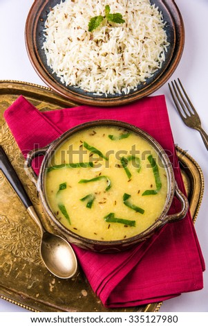Whole Yellow Lentil with Rice, dal tadka and jeera rice, Indian Dish, cooked rice and cooked Arhar or Toor dal (Pigeon Pea), served in ceramic bowl in a brass tray,  on white background  - stock photo