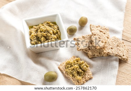 Wholegrain crackers with olive tapenade - stock photo