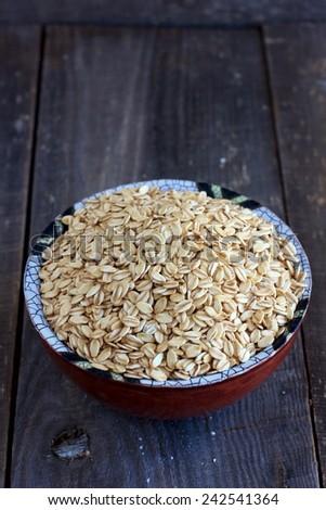 Wholegrain oat flakes in a ceramic bowl - stock photo