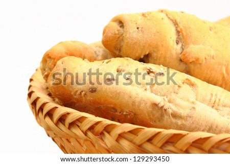wholemeal bread rolls in a wicker basket over white background