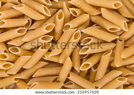 Wholemeal Pasta (Penne) for use as background image or as close-up shot - stock photo