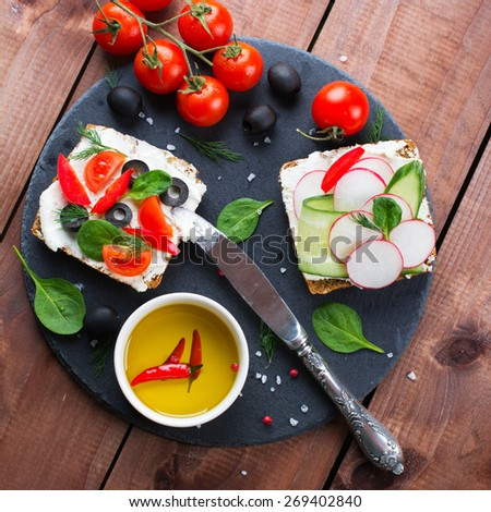 Wholemeal sandwiches with fresh vegetables on wooden background. Square image, selective focus - stock photo
