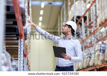 wholesale, logistic, business, export and people concept - happy man or manager with clipboard checking goods at warehouse - stock photo