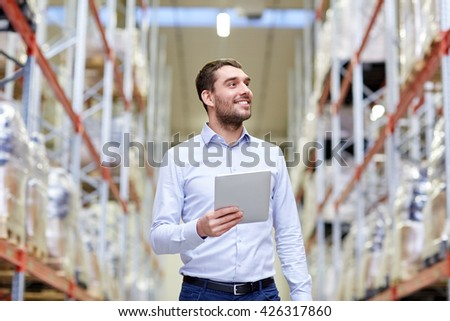 wholesale, logistic, business, export and people concept - happy man or manager with tablet pc computer checking goods at warehouse - stock photo