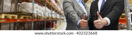 wholesale, logistic, international business, export and people concept - close up of man and woman showing thumbs up gesture over warehouse background - stock photo