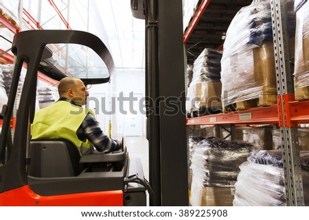 wholesale, logistic, loading, shipment and people concept - man or loader operating forklift loader at warehouse - stock photo