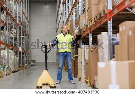 wholesale, logistic, loading, shipment and people concept - man with loader and clipboard at warehouse - stock photo