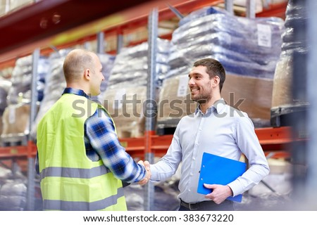 wholesale, logistic, people and export concept - manual worker and businessmen with clipboard shaking hands and making deal at warehouse - stock photo