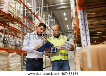wholesale, logistic, people and export concept - manual worker and businessmen with clipboard and boxes at warehouse - stock photo