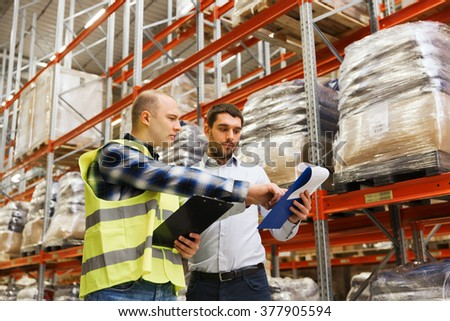 wholesale, logistic, people and export concept - manual worker and businessmen with clipboards at warehouse - stock photo