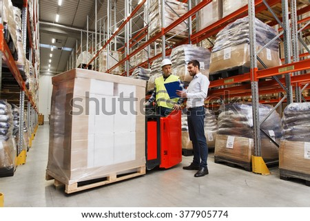 wholesale, logistic, people and export concept - manual worker on forklift loader and businessmen with clipboard at warehouse - stock photo