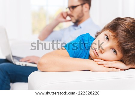 Why he always ignoring me? Busy young man working on laptop and talking on the mobile phone with his son sitting on foreground and looking upset  - stock photo