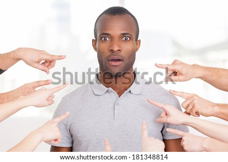 Why me? Shocked young African man looking at camera while many hands pointing him  - stock photo
