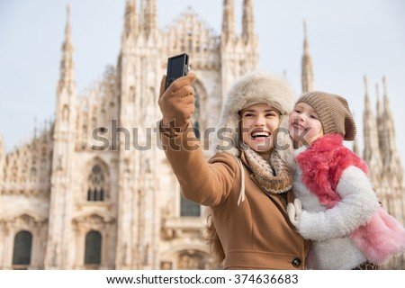 Why not to hang out in Italian fashion capital Milan on winter holidays with family. Happy mother and daughter taking selfie in front of Duomo