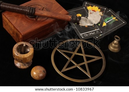 wiccan objects - brass pentacle wand wooden box bell crystal and tarot cards