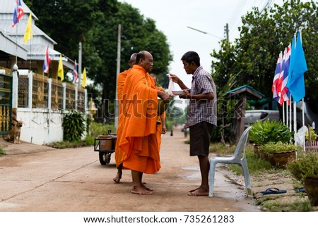 WICHIAN BURI, THAILAND - AUGUST 30,2017: A Thai man make merit and offer food to the monks on the road