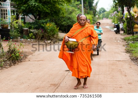 WICHIAN BURI, THAILAND - AUGUST 30,2017: Monk in a small Thai village walking on the read