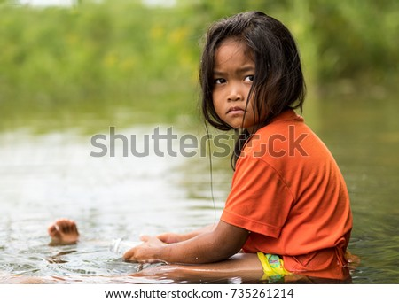 WICHIAN BURI, THAILAND - JULY 28,2017:  A small Thai girl playing in water on a sunny day