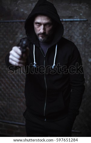 Wicked brutal criminal pointing a gun